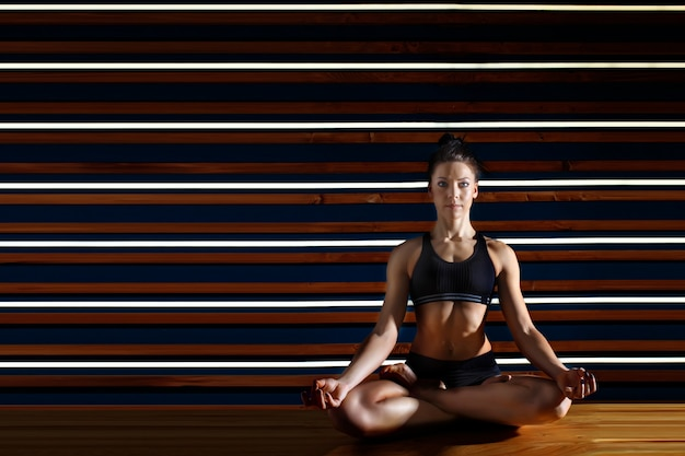 Young woman doing yoga exercises in dark studio. health lifestyle concept. Premium Photo