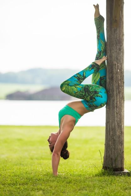 Молодая женщина делает упражнения йоги в летнем городском парке Бесплатные Фотографии
