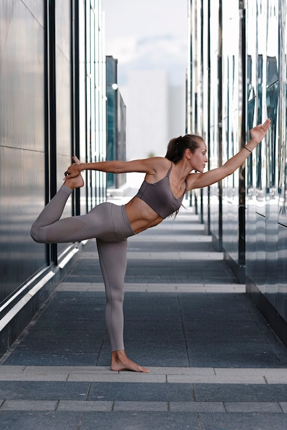 Young woman doing yoga exercises with city on background. Premium Photo