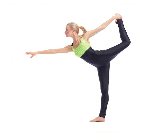 Young woman doing yoga on white balancing on one leg Free Photo