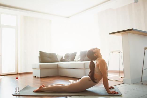 Молодая женщина делает тренировки йоги в комнате во время карантина. девушка делает вверх смотреть на позу собаки. растяжка спины и верхней части тела в домашних условиях на коврике. Premium Фотографии