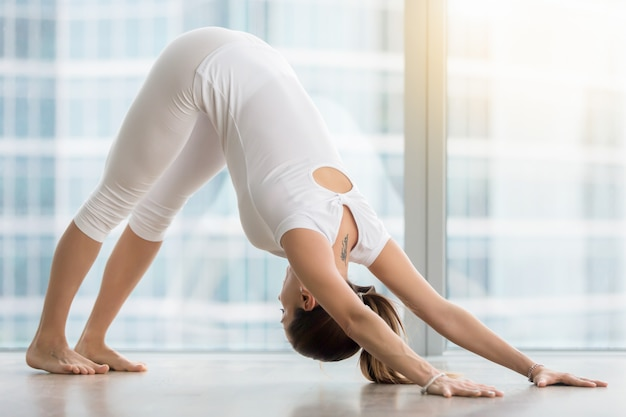 Young woman in downward facing dog pose against floor window Free Photo