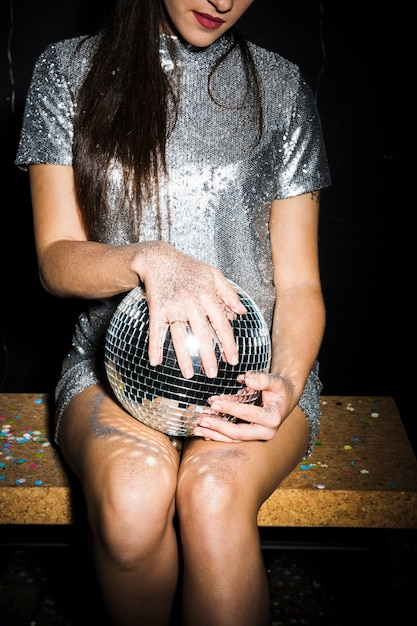 Young woman in dress with disco ball Free Photo