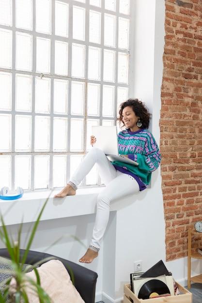 若い女性は、自宅の窓枠に座っている間、ラップトップでカジュアルに作業している服を着ています。在宅勤務のコンセプト。 Premium写真