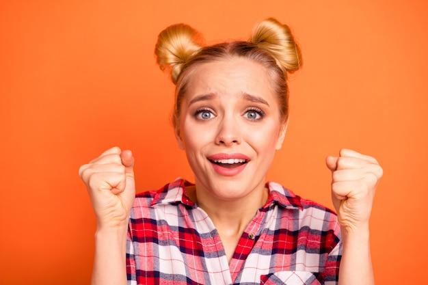 Молодая женщина, одетая в клетчатую рубашку, изолированную на оранжевом Premium Фотографии