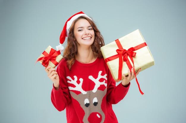 クリスマスプレゼントでサンタの帽子に身を包んだ若い女性 無料写真