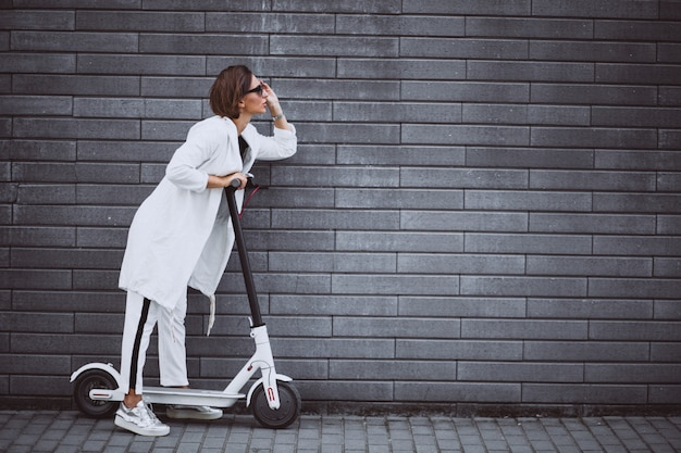 Young woman dressed in white riding scooter Free Photo
