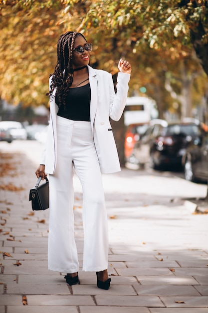 Young woman dressed in white suit outside the street Free Photo