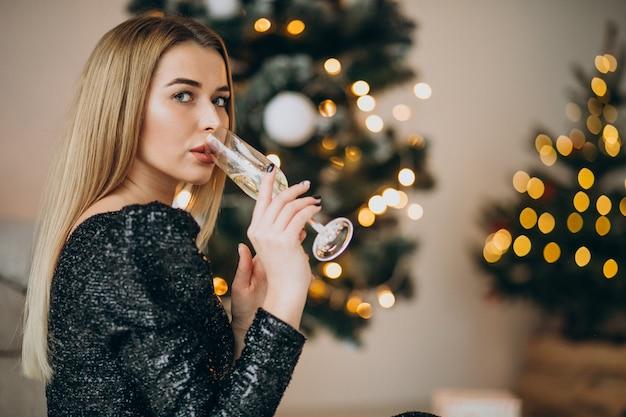 Giovane donna che beve champagne dall'albero di natale Foto Gratuite