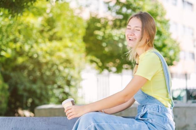 젊은 여성이 커피를 마시고 전염병 동안 공원에서 웃고 프리미엄 사진