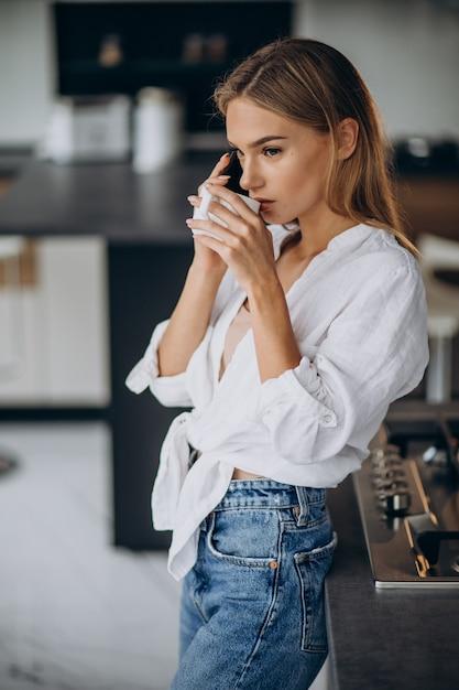 キッチンでコーヒーを飲む若い女性 無料写真