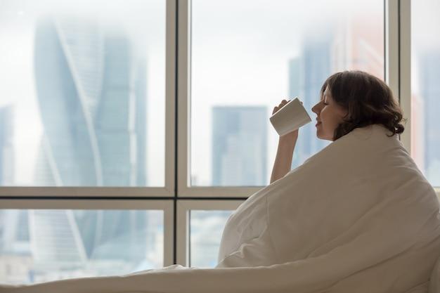 mulher debaixo das cobertas tomando bebida em xícara