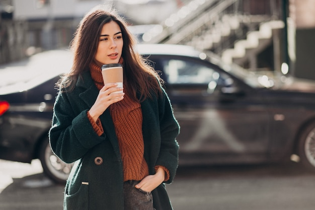 Young woman drinking coffee by her car Free Photo