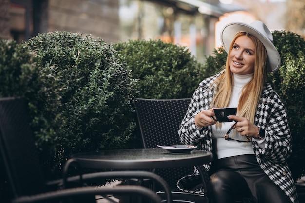 Giovane donna che beve il caffè in un caffè Foto Gratuite