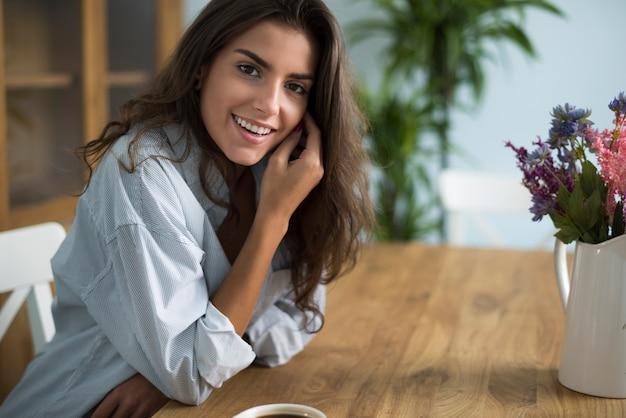 ダイニングルームでコーヒーを飲む若い女性 無料写真