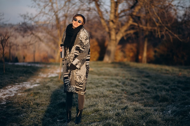 Молодая женщина пьет кофе утром и гуляет в парке Бесплатные Фотографии