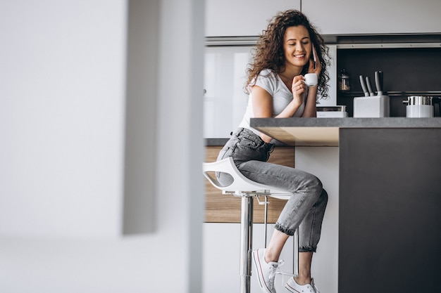 Young woman drinking coffee at the kitchen Free Photo