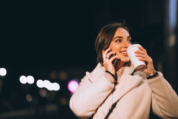 Young woman drinking coffee at night street Free Photo