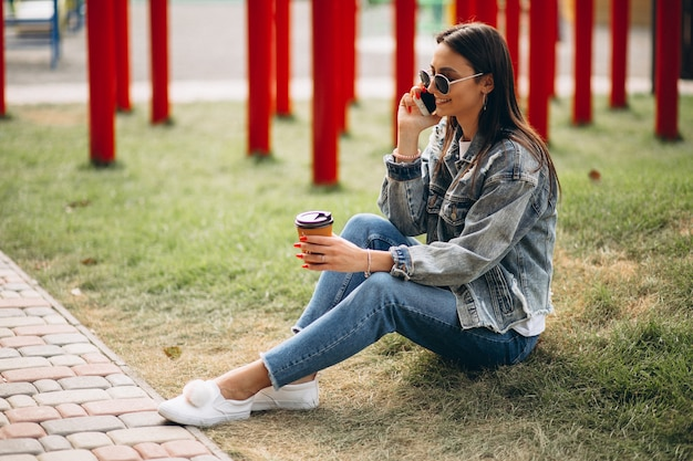 Young woman drinking coffee in park Free Photo