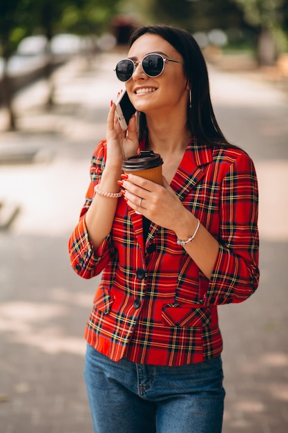 Young woman drinking coffee and talking on the phone Free Photo