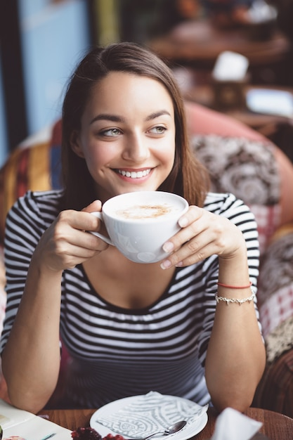 Young woman drinking coffee in urban cafe Free Photo