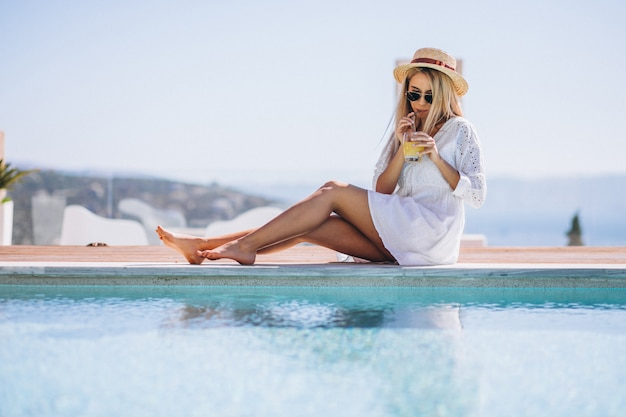 Young woman drinking juice bu the pool Free Photo