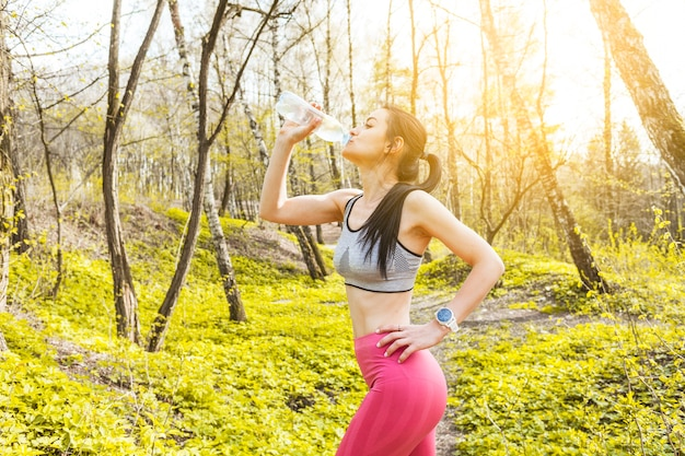 Young woman drinking water in the nature Free Photo