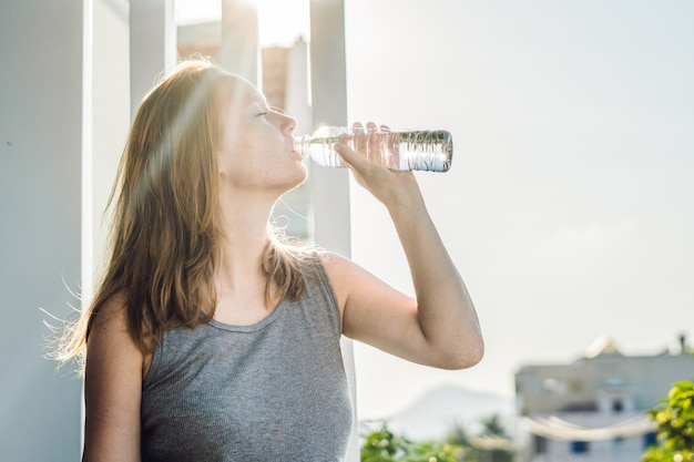 Young woman drinking water in the sunlight Premium Photo