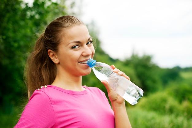 Acqua potabile della giovane donna Foto Gratuite