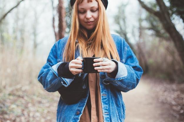 La giovane donna beve la tazza di caffè sulla riva del lago Foto Gratuite