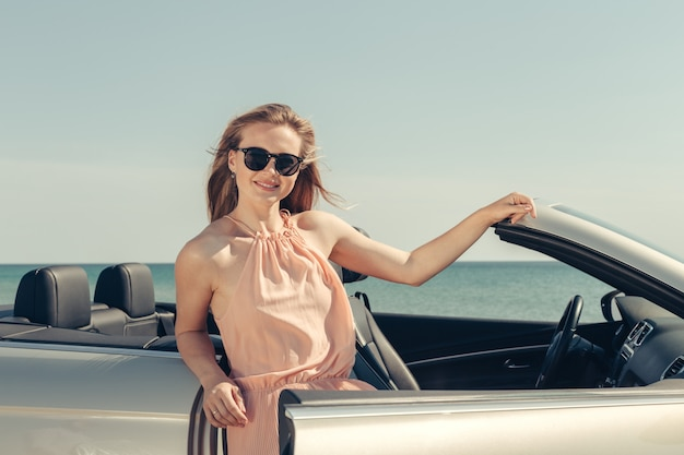 Young woman drive a car on the beach Premium Photo
