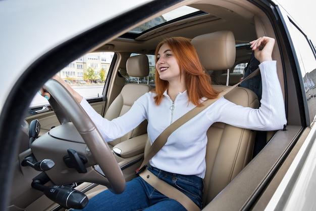 車を運転するシートベルトで固定された若い女性ドライバー Premium写真