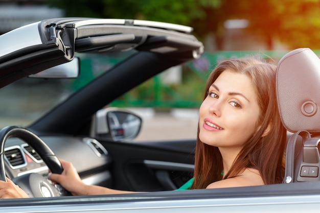 Young woman driving a car in the city. Premium Photo