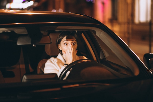 Young woman driving in car at night Free Photo