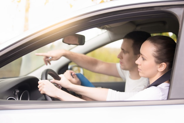 Young woman driving, man pointing the direction Free Photo