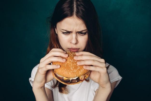 ハンバーガーを食べる若い女性 Premium写真