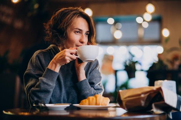 카페에서 크루아상을 먹는 젊은 여자 무료 사진