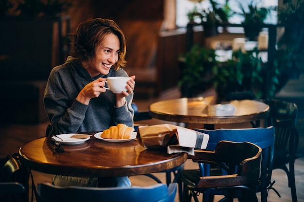 Young woman eating croissants at a cafe Free Photo