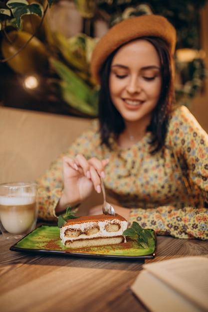 Молодая женщина ест вкусный тирамису в кафе Бесплатные Фотографии