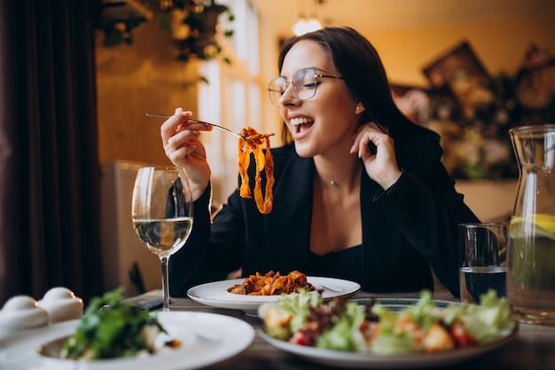 カフェでパスタを食べる若い女性 無料写真