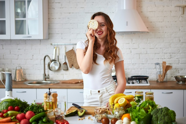 Young woman eating rye cracker crisp bread in the kitchen. healthy lifestyle. health, beauty, diet concept. Premium Photo