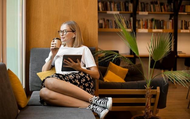 図書館でコーヒーを楽しんでいる若い女性 無料写真