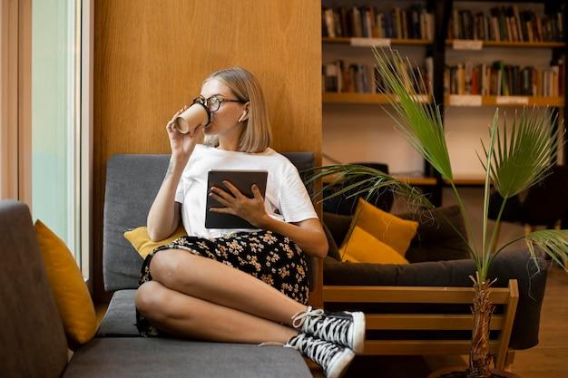 Giovane donna che gode del caffè in biblioteca Foto Gratuite