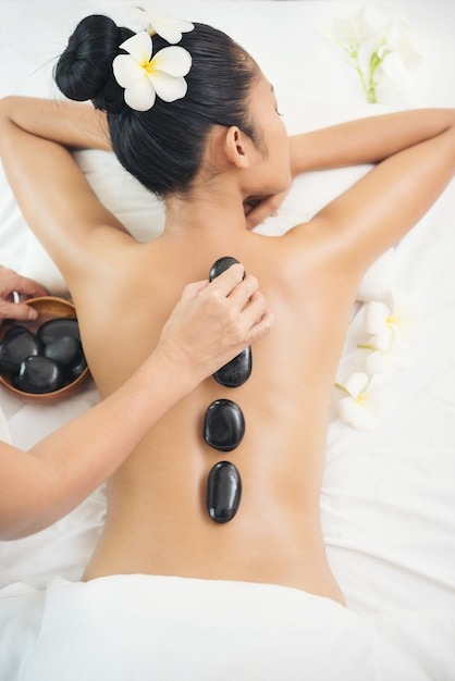 Young woman enjoying a hot rock massage in a spa salon Premium Photo