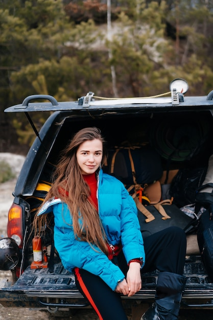 Young woman enjoying nature while sitting in the car trunk Free Photo