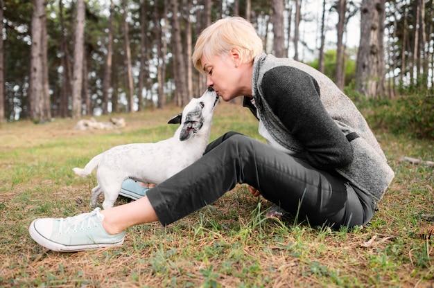 Giovane donna che gode della natura con il suo cane Foto Gratuite