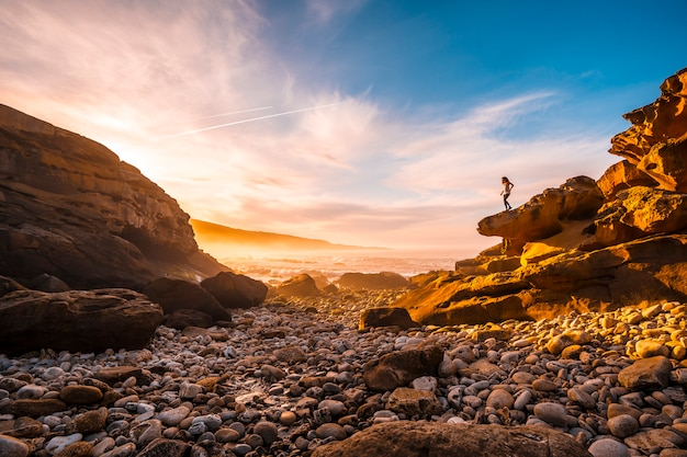A young woman enjoying the orange sunset on the coast of mount jaizkibel near san sebastian, gipuzkoa. spain Premium Photo