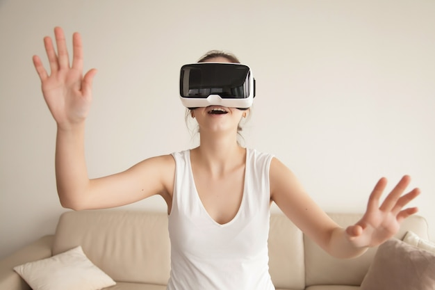 411bc2769d92 Young woman enjoys vr gaming on sofa at home Free Photo