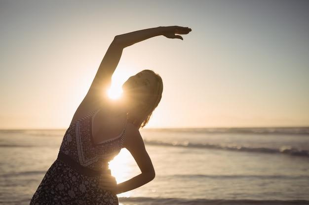 Young woman exercising at beach Free Photo