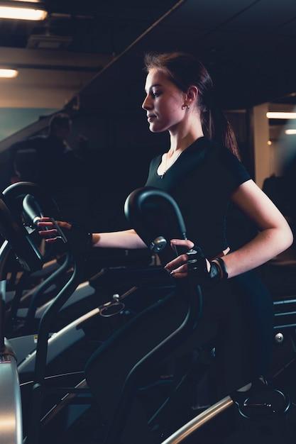 Young woman exercising on elliptical cardio machine Free Photo